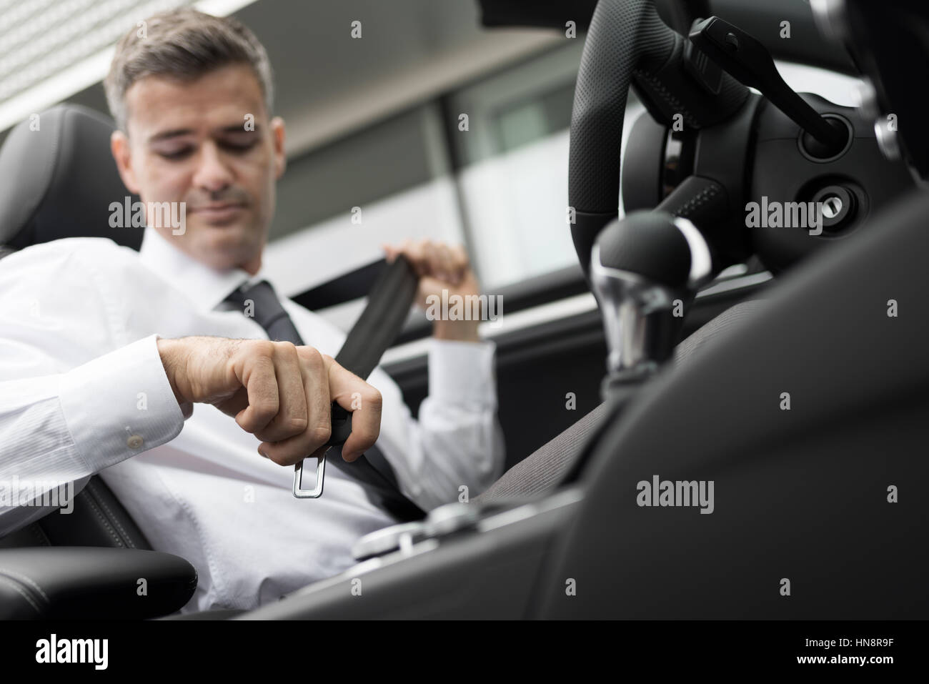 Businessman in his car fastening the seatbelt, safe driving concept - Stock Image