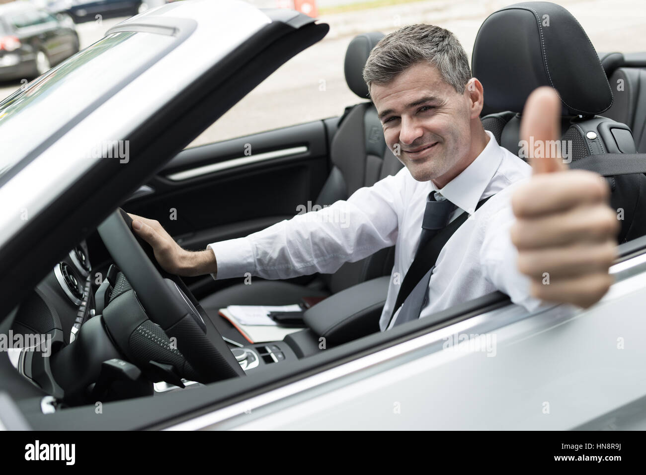 Smiling successful man driving his new expensive car and giving a thumbs up - Stock Image