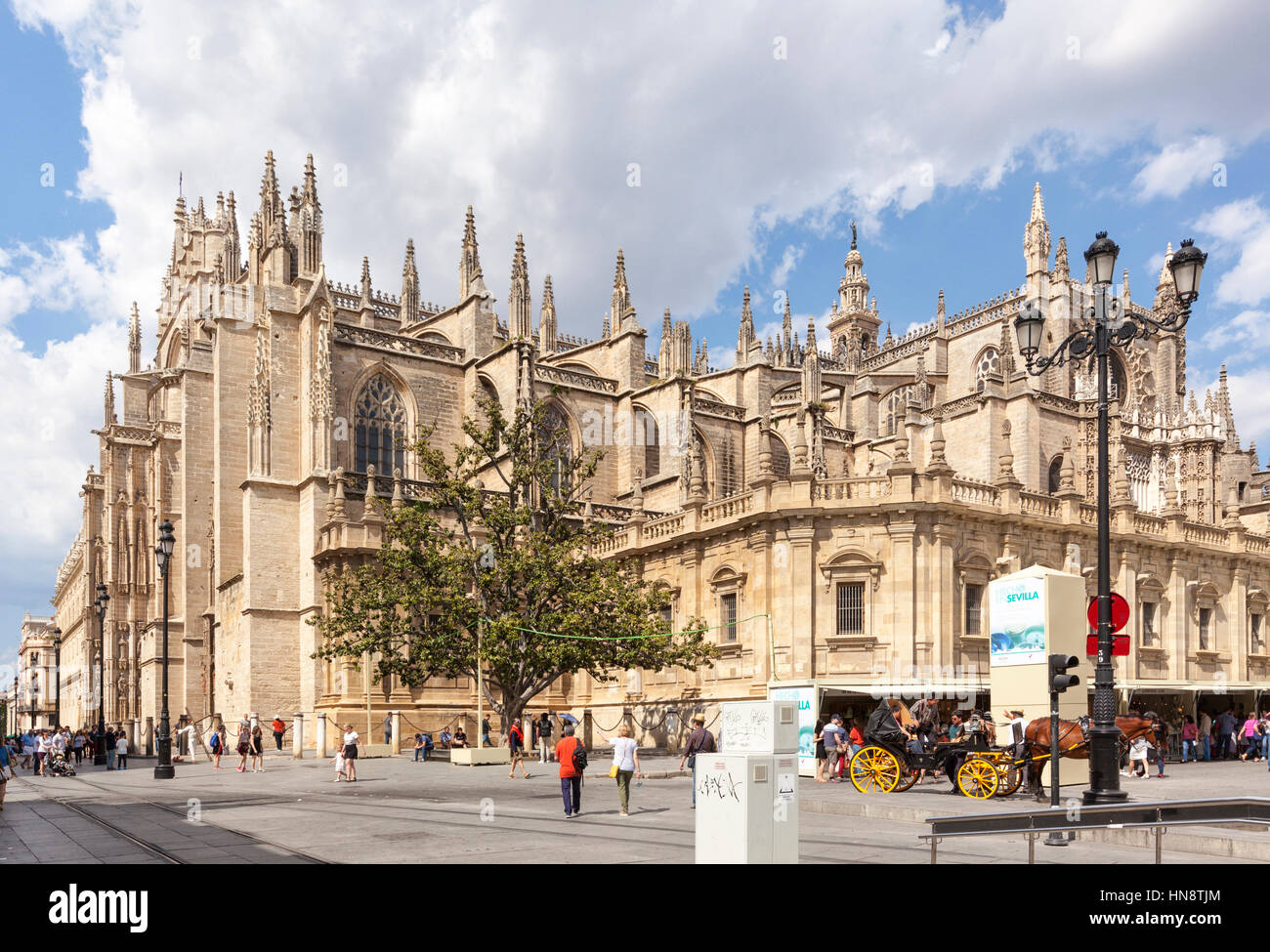 Seville, Spain - April 30, 2016: The Seville Cathedral, view from the south, horse-drawn carriage in front, people - Stock Image