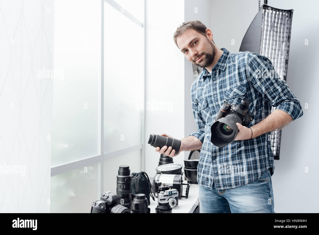 Photographer in his studio, he is holding a digital camera and choosing the right lens for his photo shoot Stock Photo
