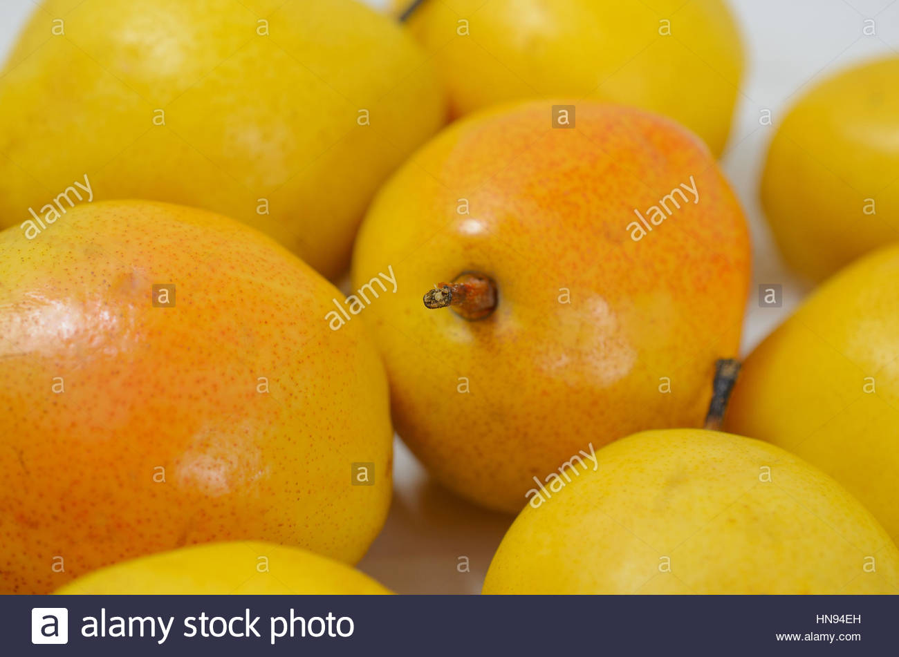 yellow pears on a white wooden background - Stock Image