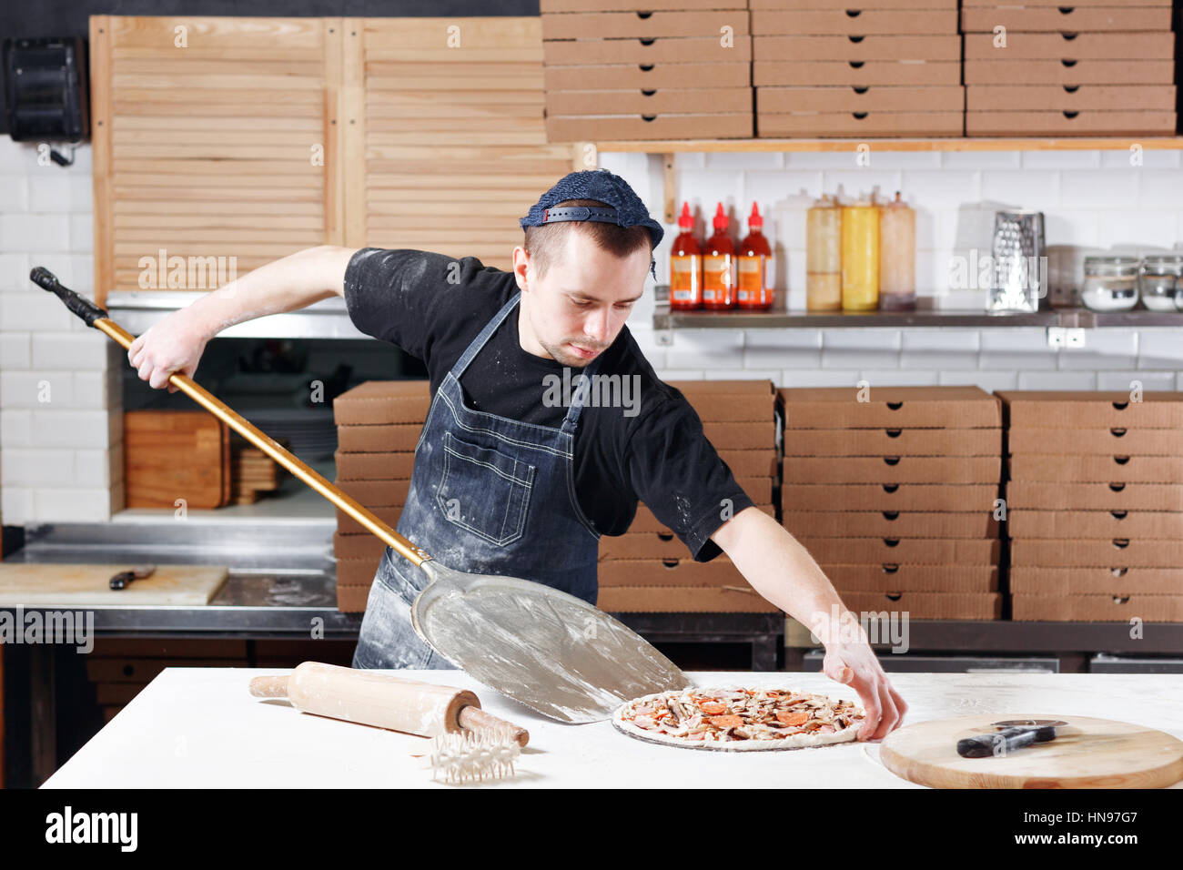 Cook In A Blue Apron In The Kitchen. With A Shovel In His Hands. Boxes For  Food Delivery On Background.