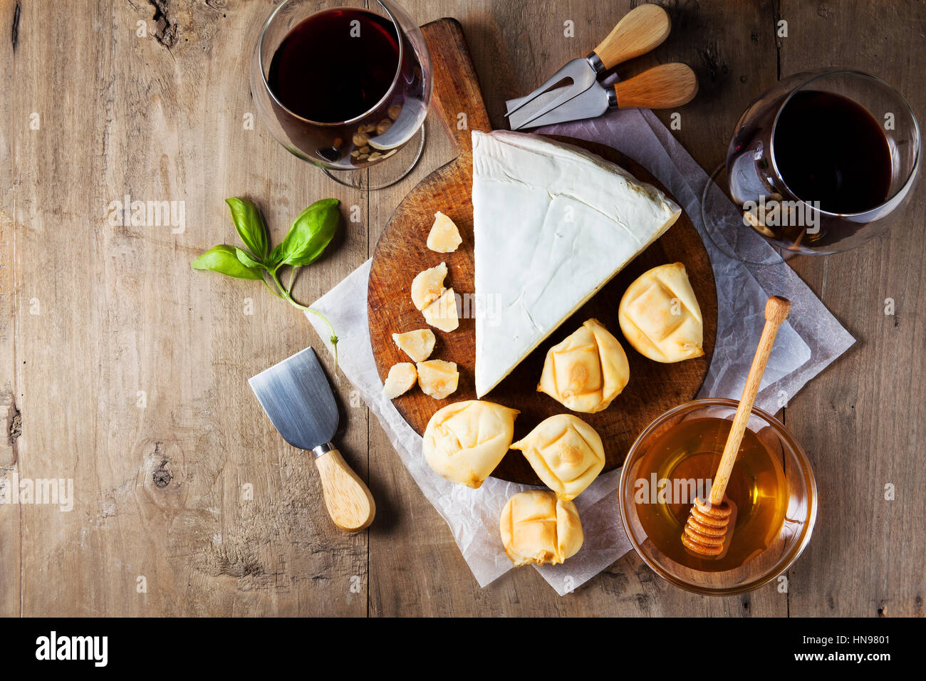 Cheese plate Assortment of various types of cheese and honey on wooden cutting board Stock Photo