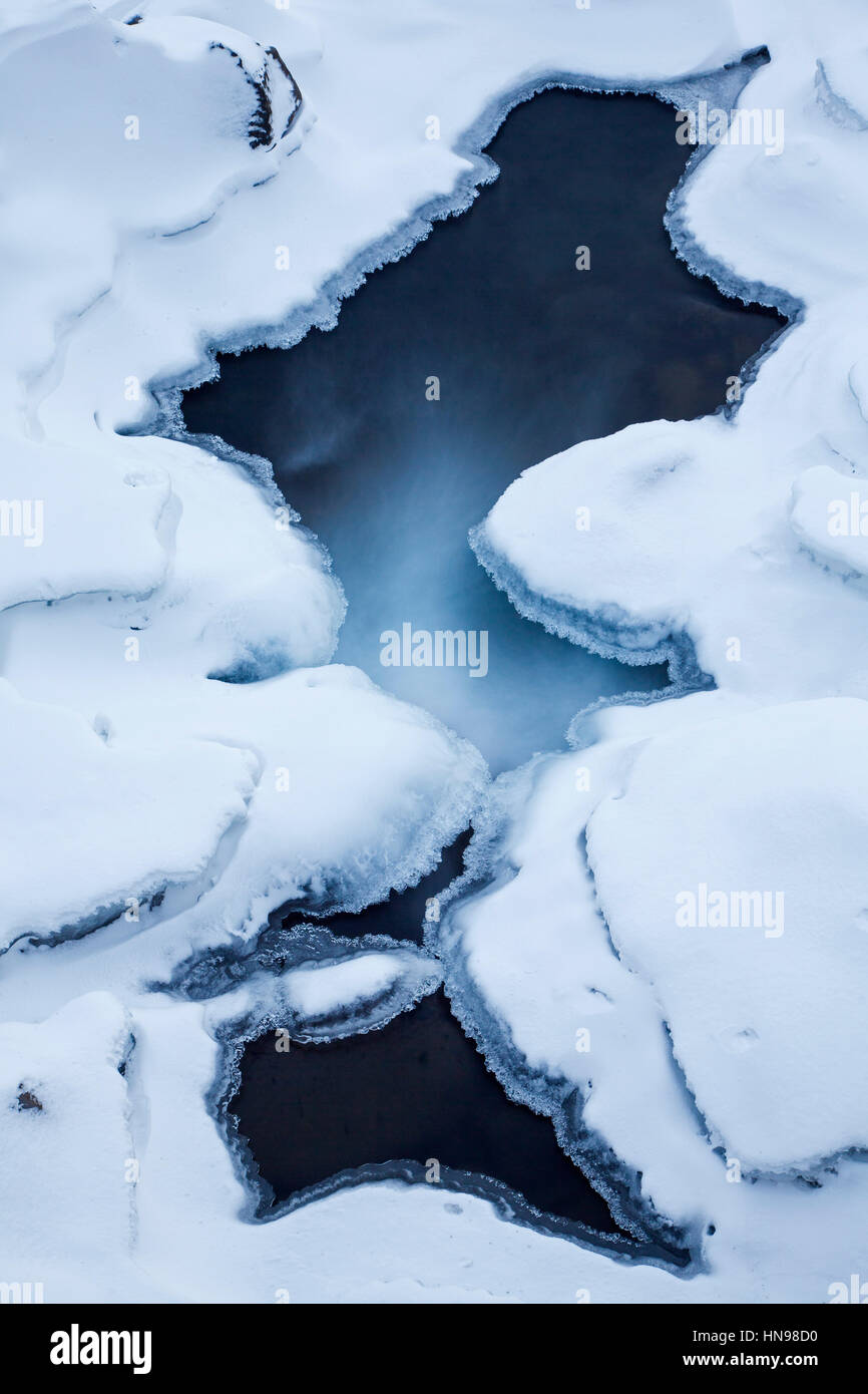Ice formations formed by frost and freezing cold temperatures over running water of stream - Stock Image