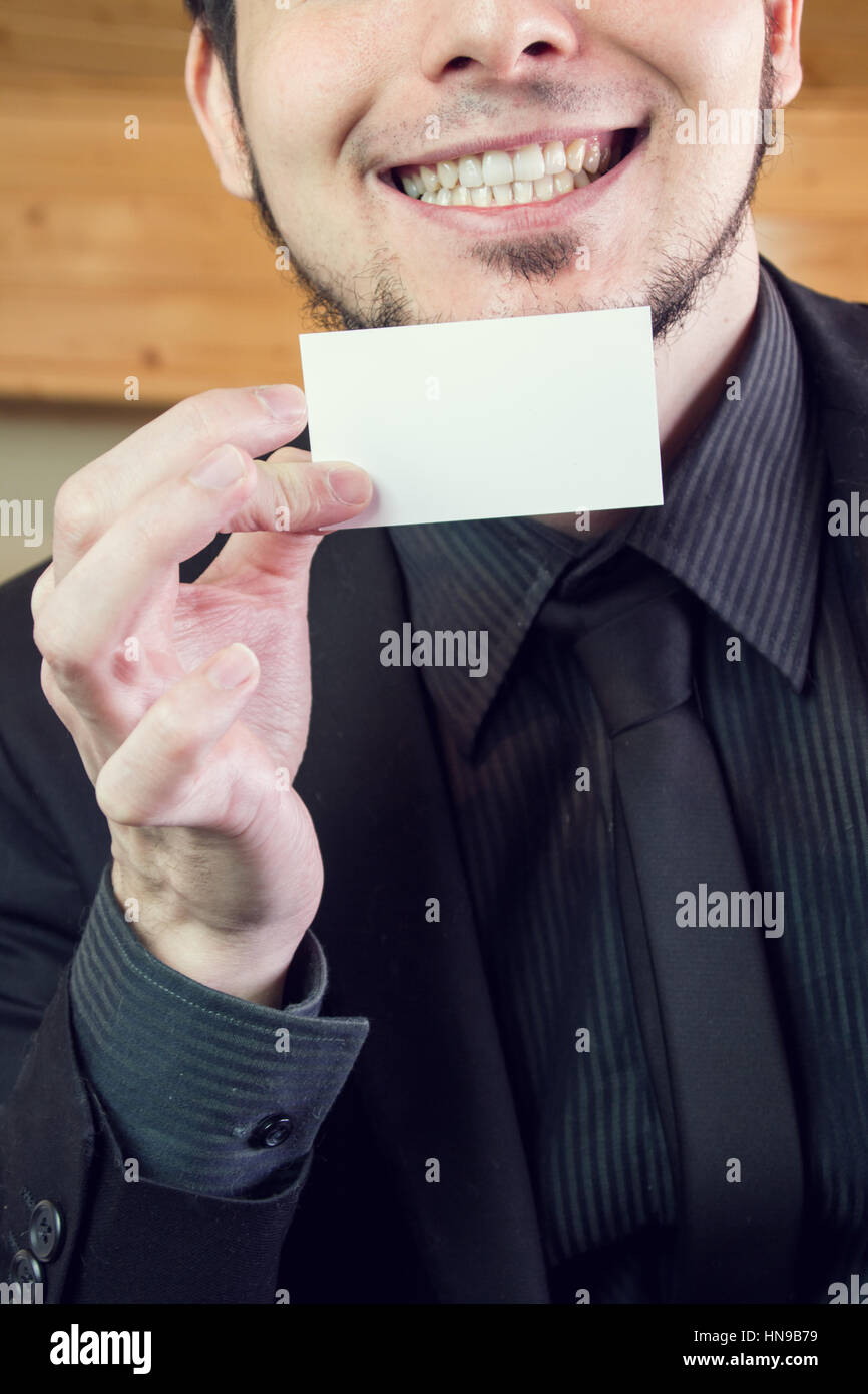Young businessman showing his calling card - Stock Image