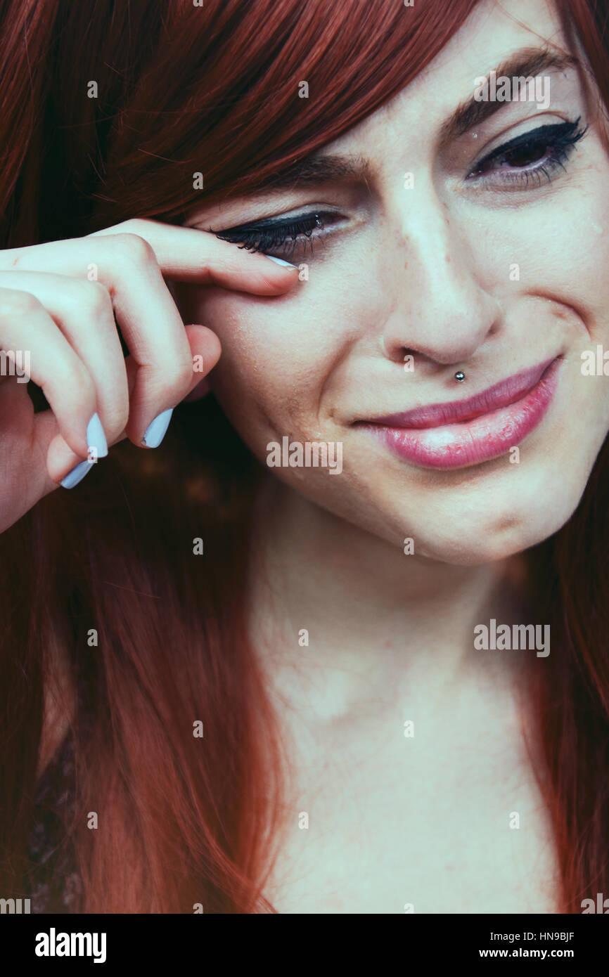 Young redhead woman crying - Stock Image