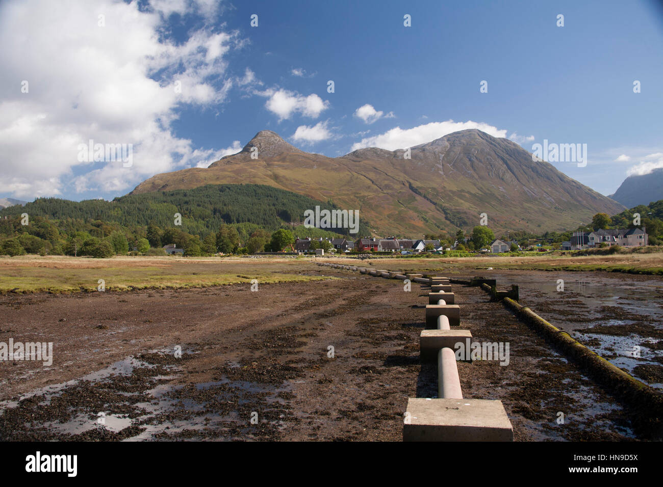 Large pipes leading from Loch Leven towards Glen Coe Village with Pap of Glen Coe mountain, majestic highlands at - Stock Image