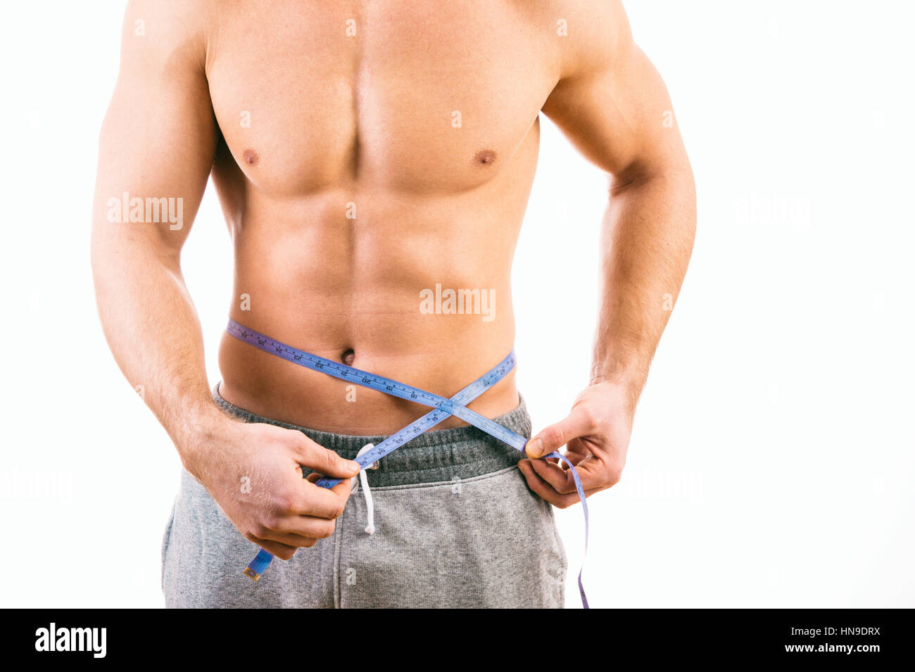 Male torso and blue tape measure on white background - Stock Image