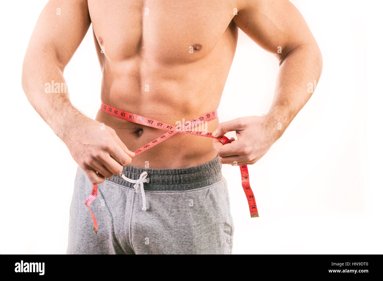 Male torso and red tape measure on white background - Stock Image