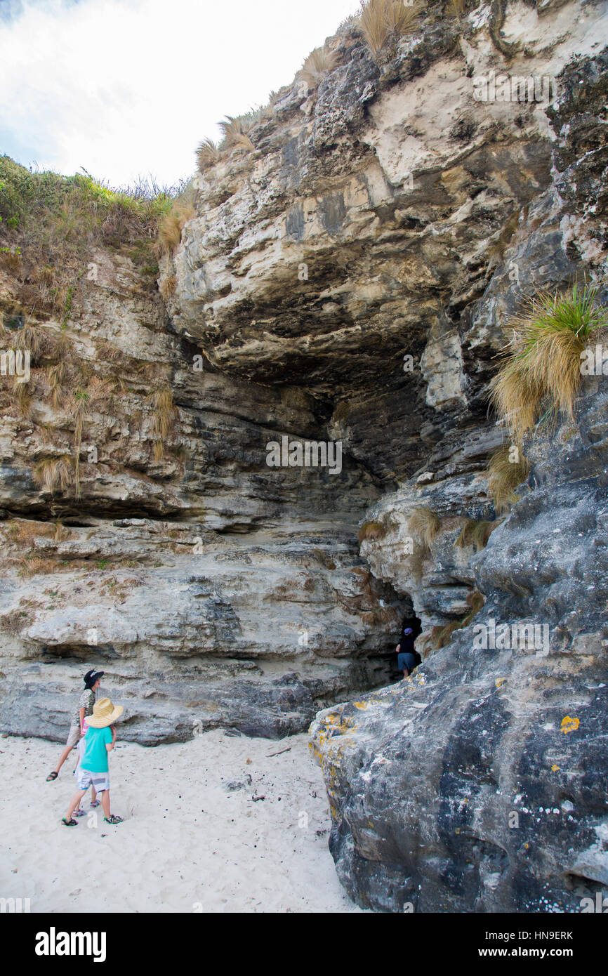 Children walking into cave  in the rock at Cave Beach,Booderee national park,Jervis Bay Territory, east coast Australia - Stock Image
