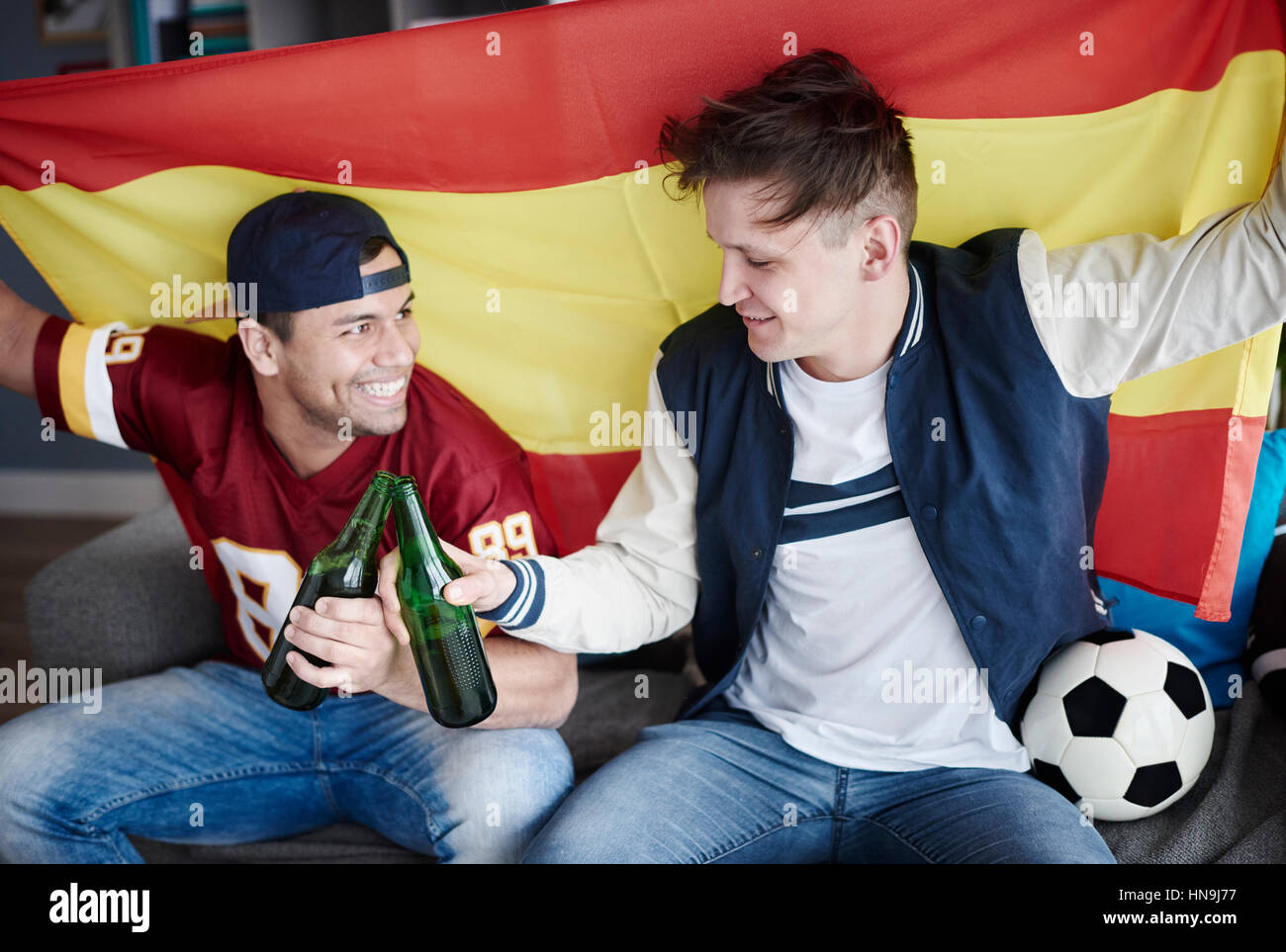 Two friends enjoying soccer on television - Stock Image