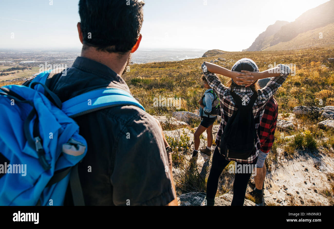 Rear view shot of young people walking in countryside. Group of friends hiking in nature. Stock Photo