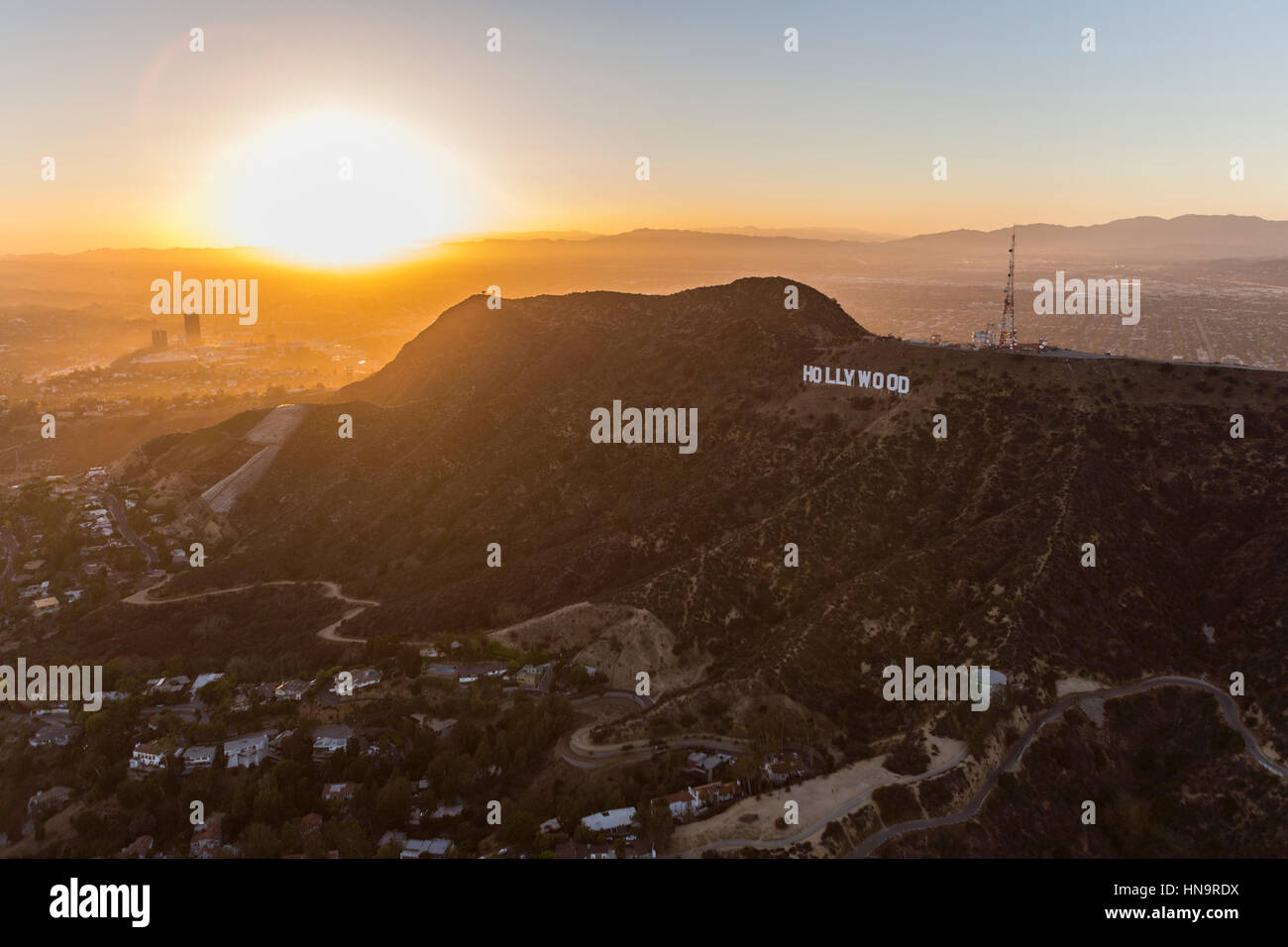 Los Angeles, California, USA - July 21, 2016:  Aerial of sun setting behind the Hollywood Sign on Mt. Lee in Griffith Stock Photo