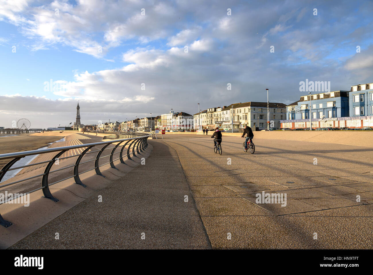 Couple of bicycle riders enjoy a ride on the South promenade at Blackpool beach, England. - Stock Image