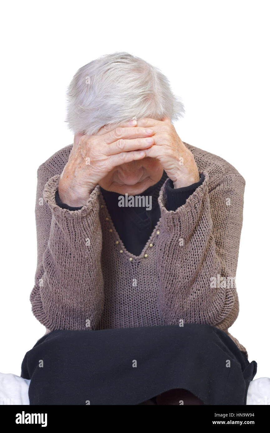 Elderly wrinkled woman sitting lonely on the bed - Stock Image