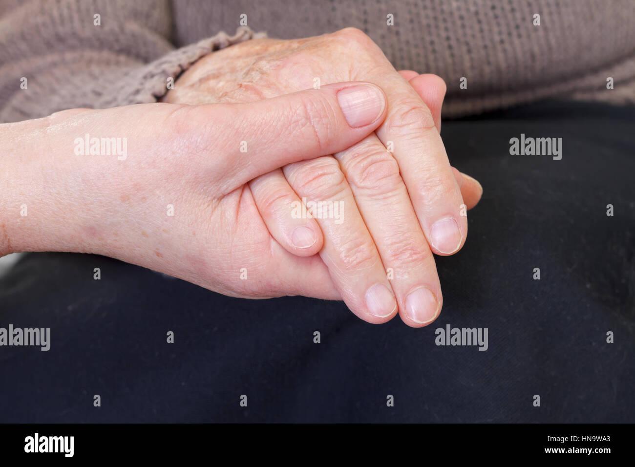 Doctor or nurse holding elderly wrinkled hand - Stock Image