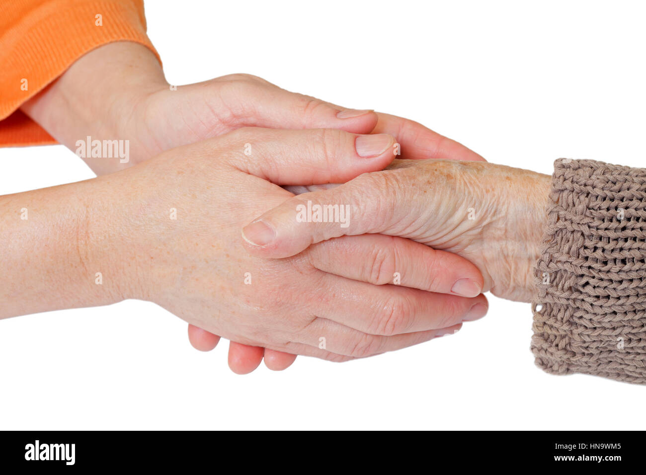 Woman holding elderly hands on isolated background - Stock Image