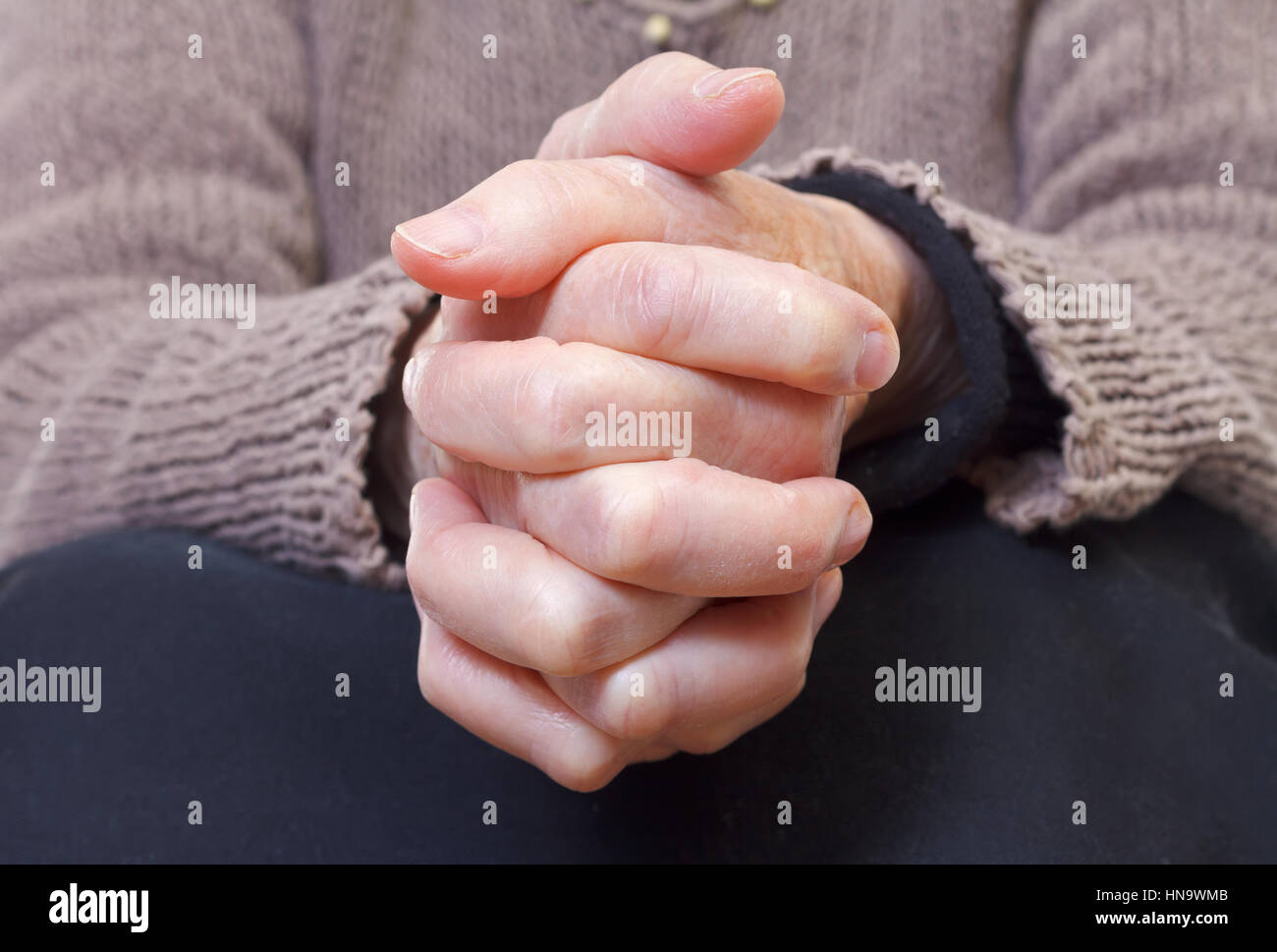 Close up of an elderly woman holding her hands - Stock Image