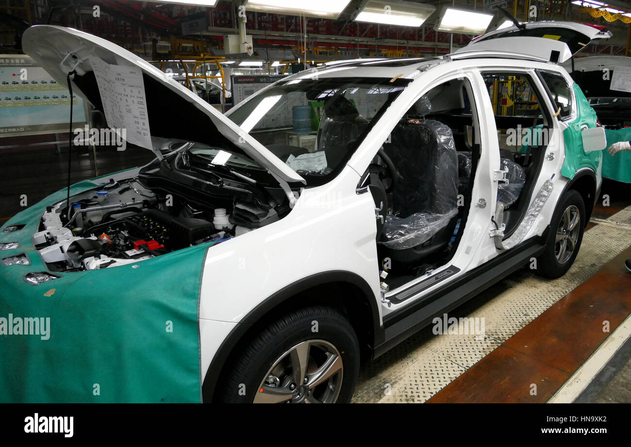 Tianjin, China. December 17th 2016: Workers assemble a car on assembly line in car factory - Stock Image