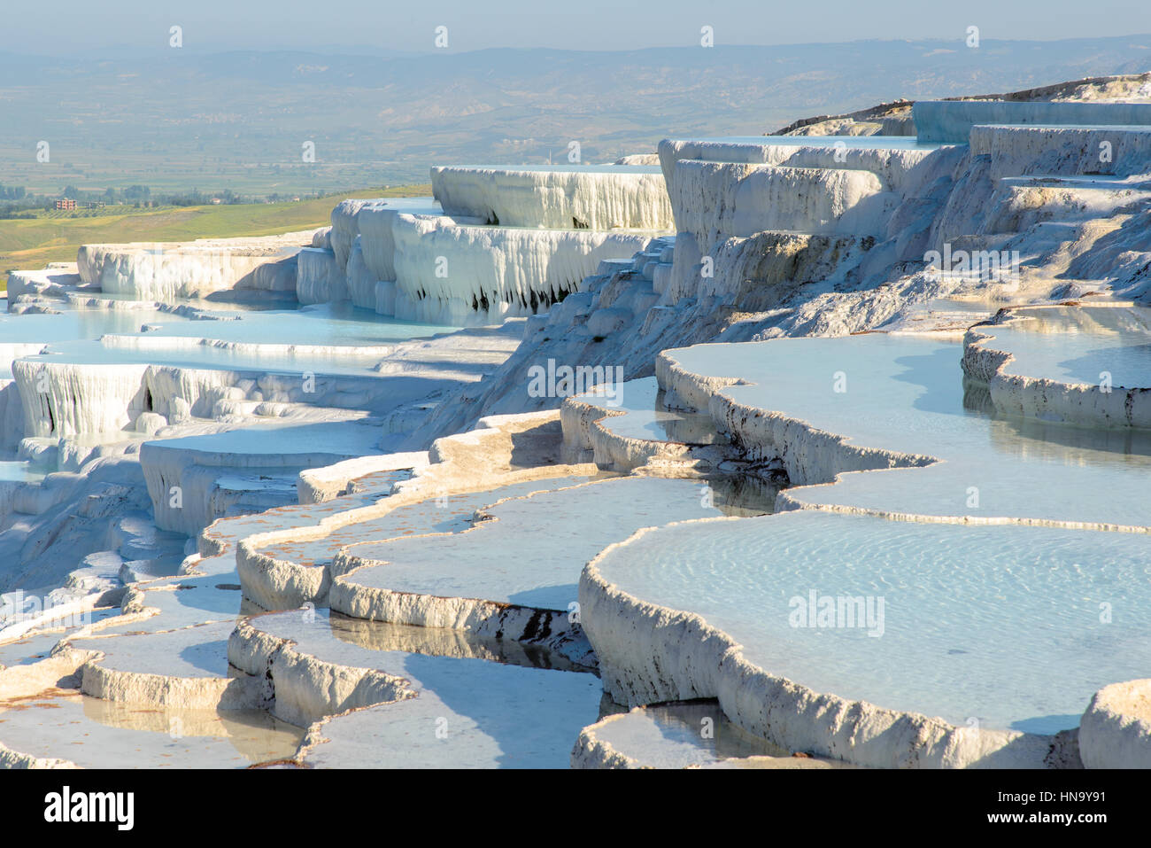 The enchanting pools of Pamukkale in Turkey. Pamukkale contains hot springs and travertines, terraces of carbonate - Stock Image