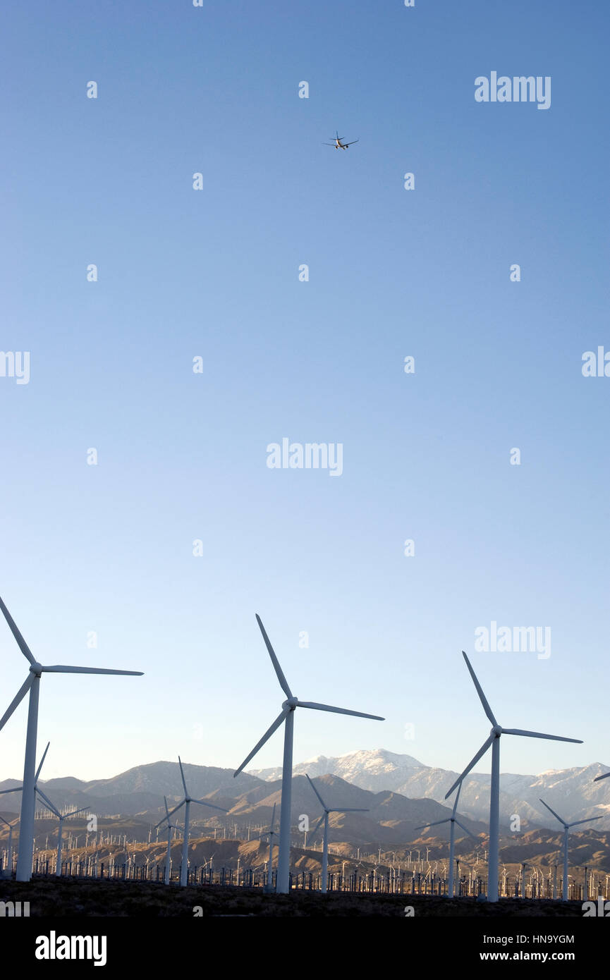 Plane flying over wind mills and snow capped mountains in the Palm Desert near Palm Springs, CA - Stock Image