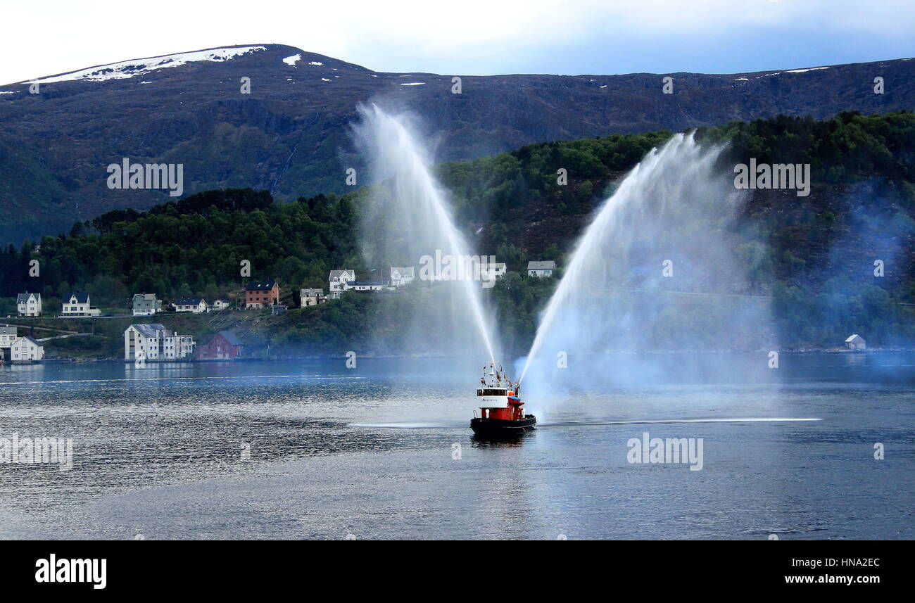 A pilot boat sprays water with its water canon to salute a cruise ship in the harbor of Alesund in Norway image - Stock Image