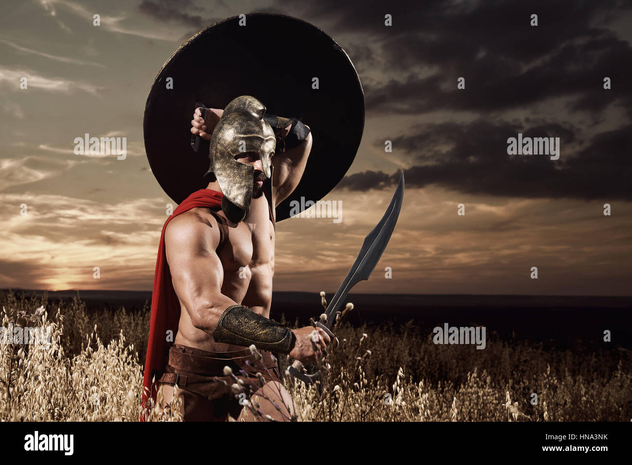 Spartan warrior going forward in attack with sword. - Stock Image