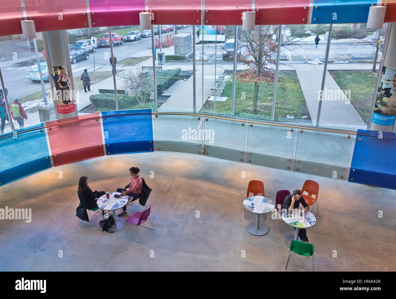 People sitting at small round tables in the atrium of the Blusson spinal cord centre in Vancouver - Stock Image