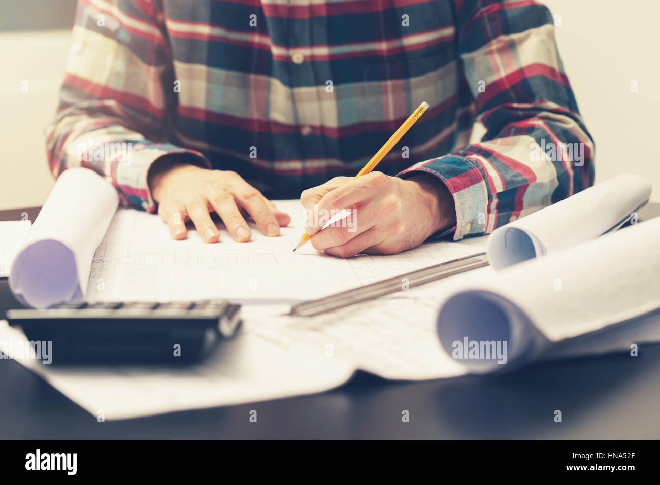construction engineer working on blueprint at his workplace in office - Stock Image