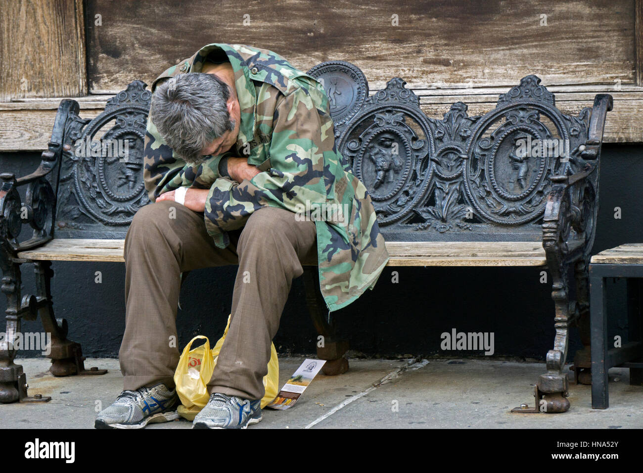 An anonymous  middle aged man - possibly a veteran - sitting with anguished body language on a bench in NOLITA, - Stock Image