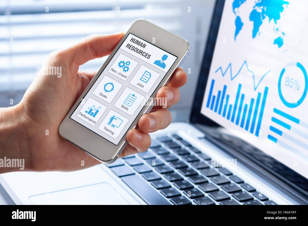 Human resources (HR) management app concept on a mobile phone screen with a person hand and office interior background, Stock Photo