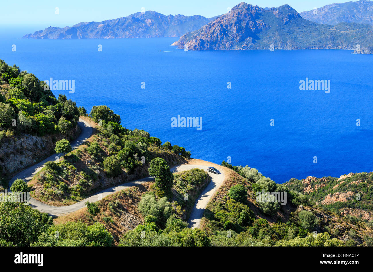 Red Car on hairpin bend overlooking The Gulf Of Porto looking towards Scandola , Corsica, France - Stock Image
