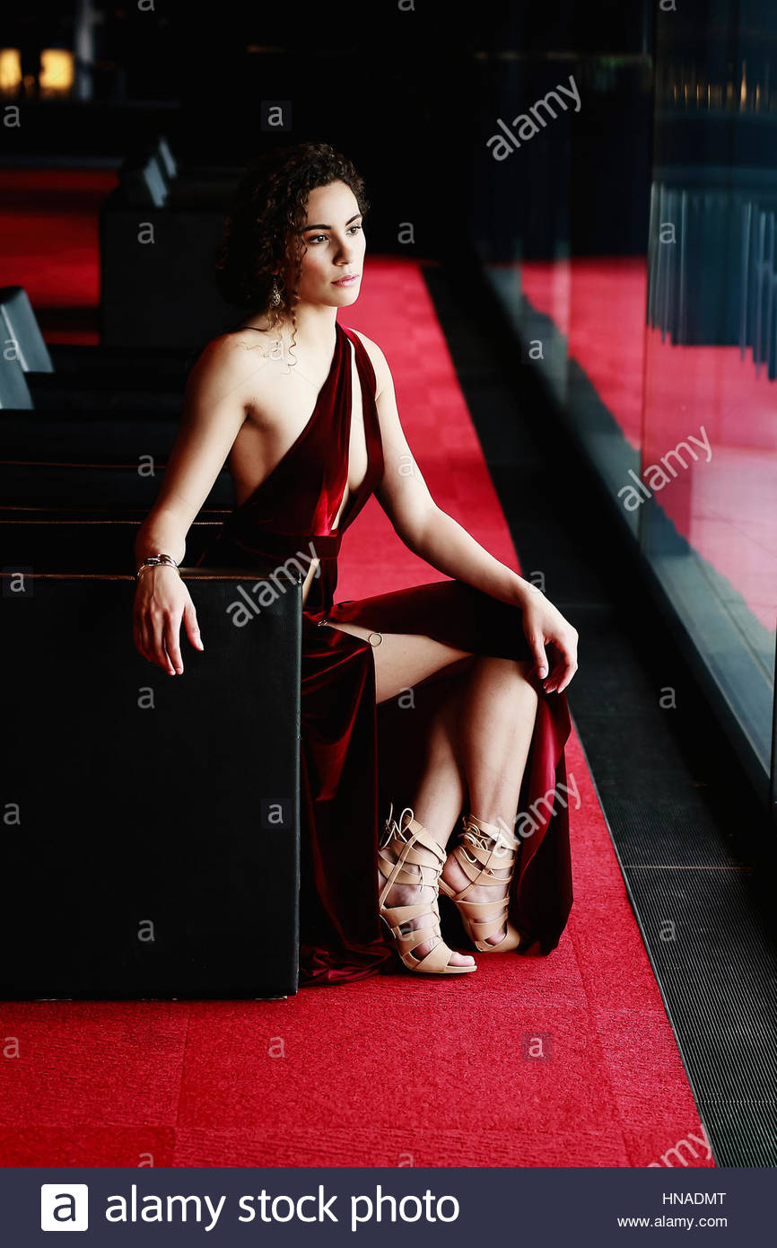 Elegant young woman in a red dress - Stock Image