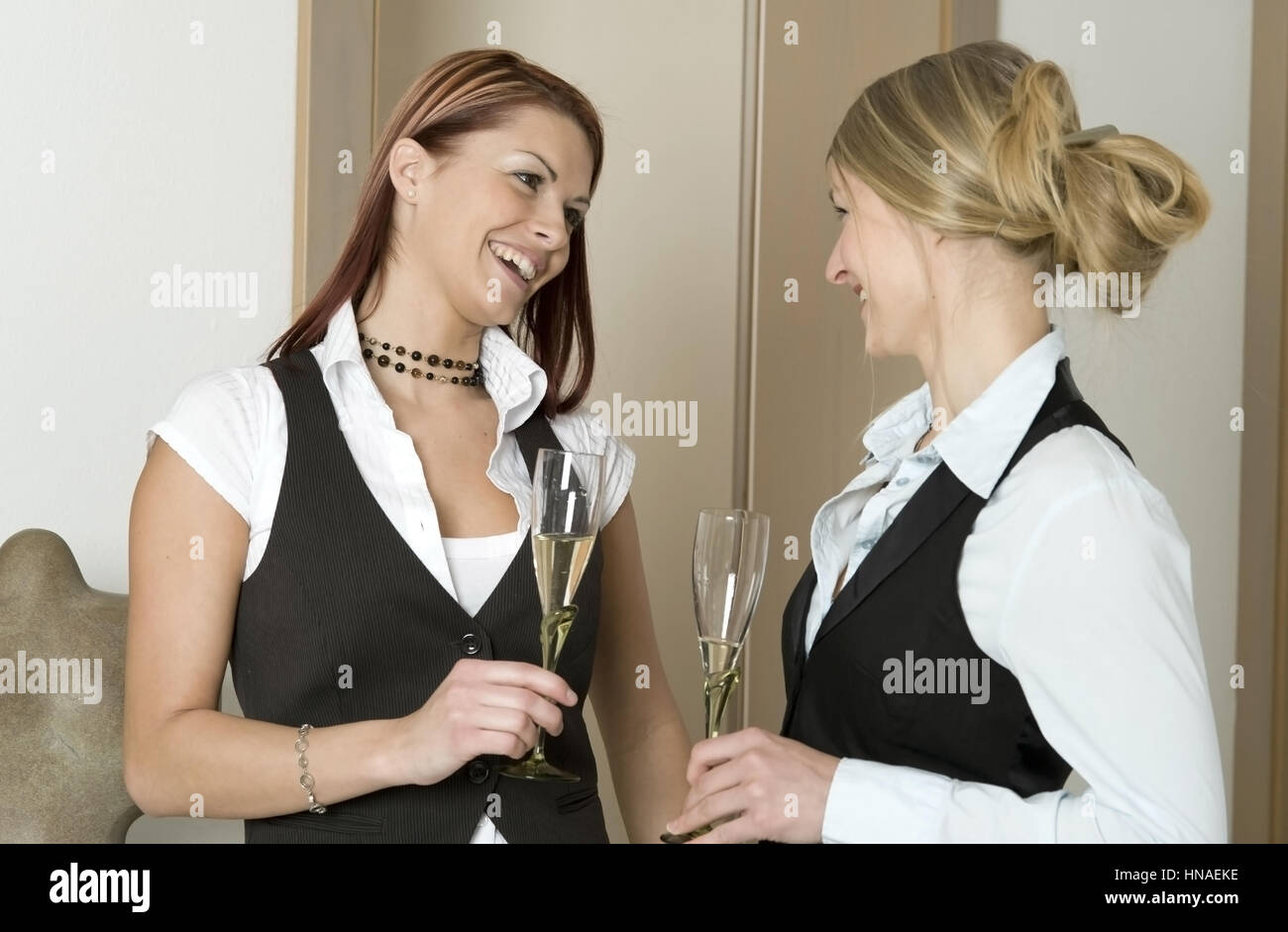 Zwei junge Frauen mit Sektglaesern in Haenden - two young women with sparkling wine - Stock Image