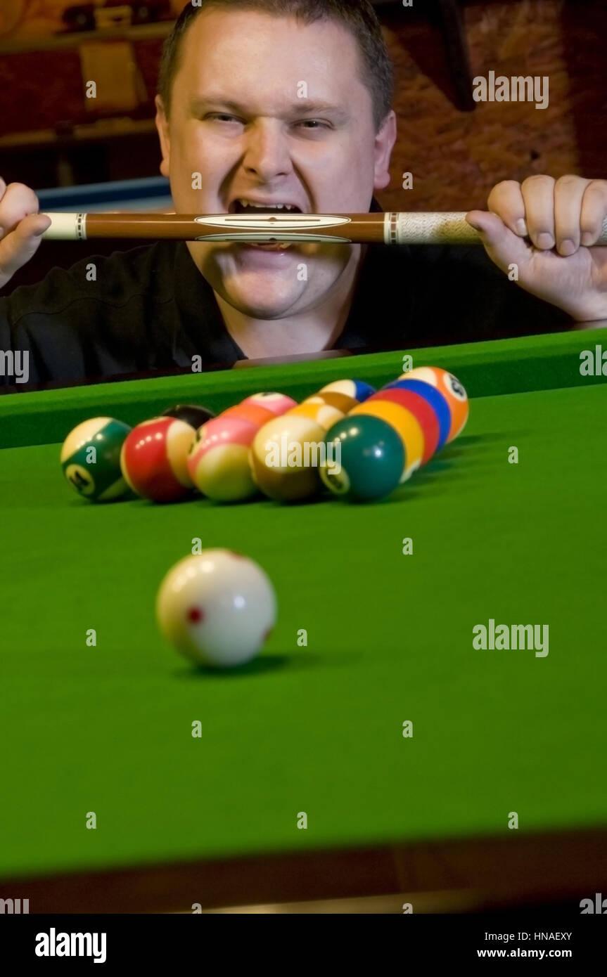 Billardspieler beisst in Billardqueue - billiard player - Stock Image