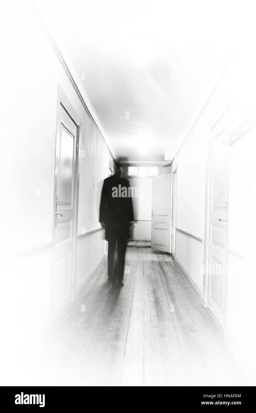 Man in black motion blur walking in a white hospital coooridor