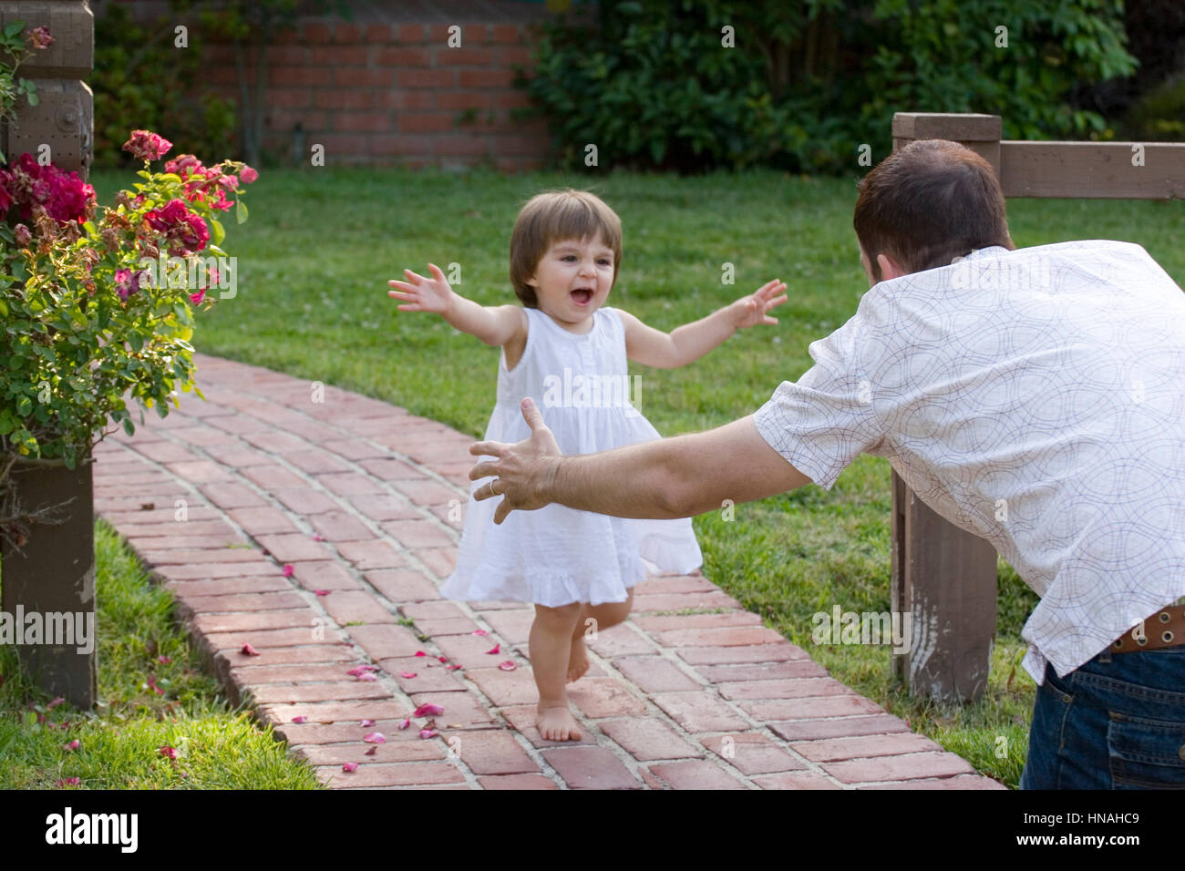 Portrait of a happy little girl running to her father. Stock Photo