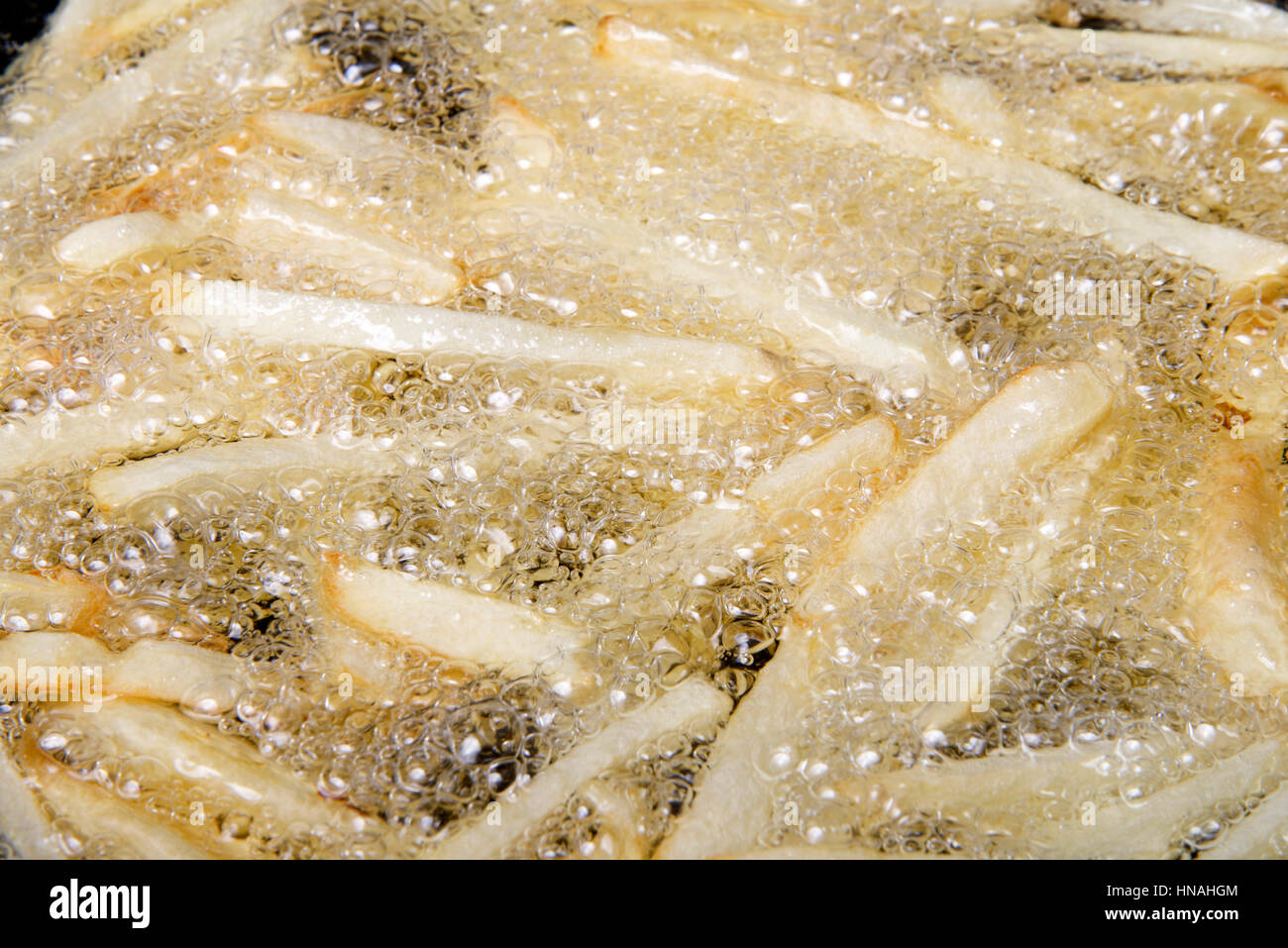Medium sized Russet potatoes peeled, sliced and frying in hot oil creating home made french fries. An inexpensive Stock Photo