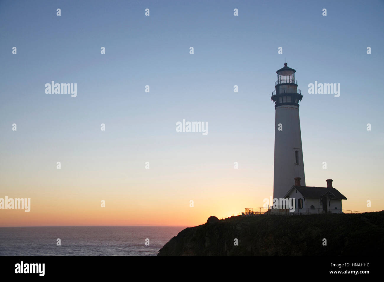 Historic lighthouse on a hill top on the coast of Northern California at Sunset, sun setting behind the light house Stock Photo