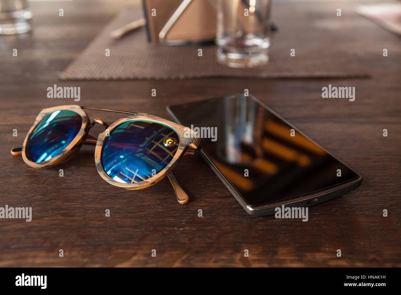 Smart phone and hipster sunglasses on wood bar table, blank screen and selected focus - Stock Image