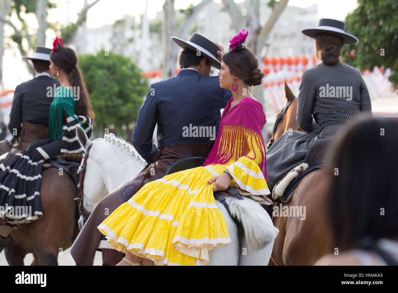 SEVILLE, SPAIN - APR, 25: people dressed in traditional costumes riding horse at the Seville's April Fair on - Stock Image