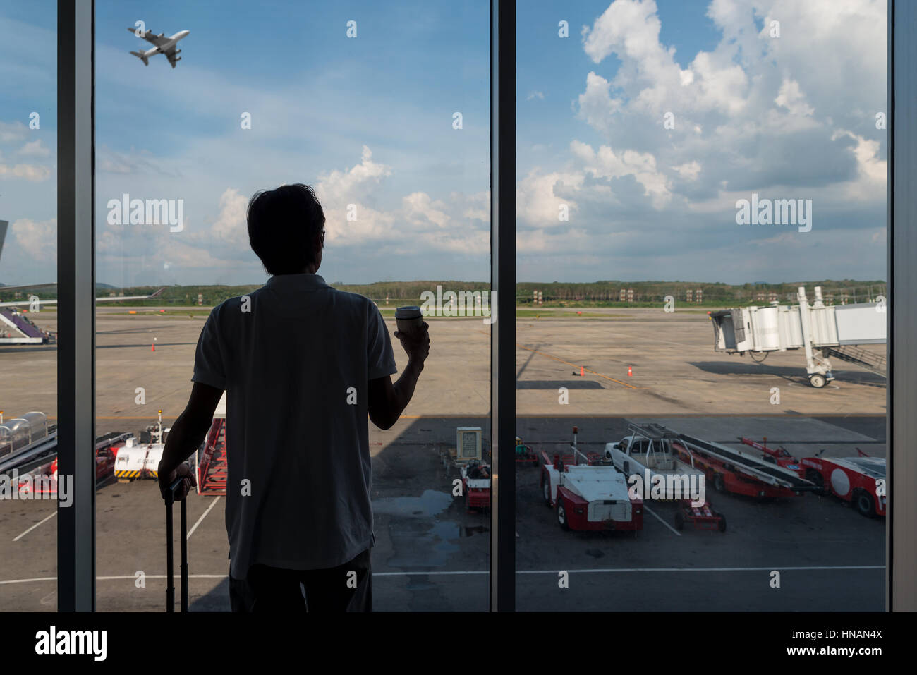 Back side of traveler boy in termainal at airport looking at the flying plane above airport, travel and vacation - Stock Image