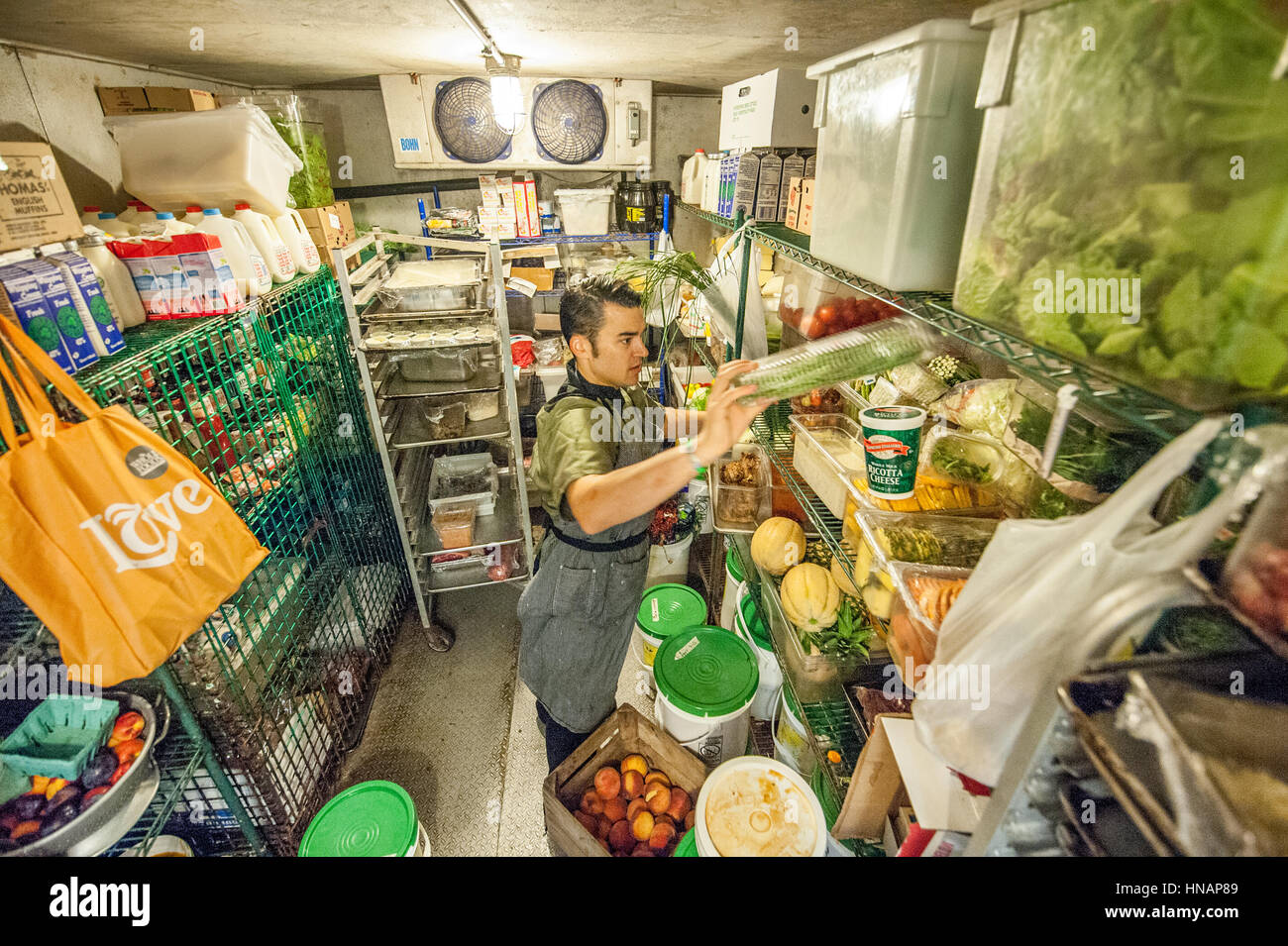 a food worker placing fresh produce in the walk in refrigerator at gertrudes restaurant in baltimore maryland - Walk In Refrigerator