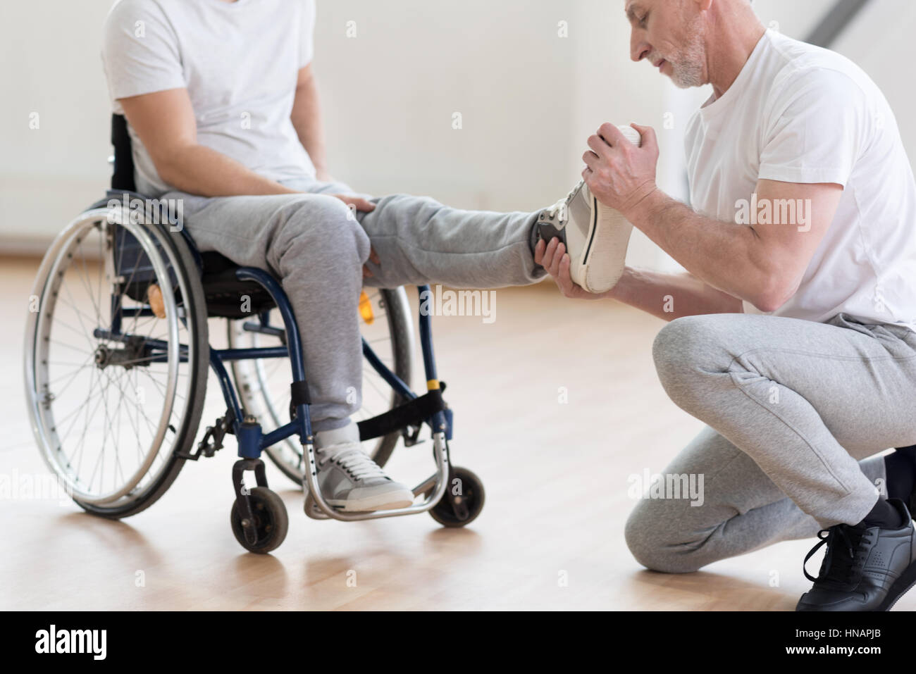 Aged orthopedist working with handicapped in the gym - Stock Image