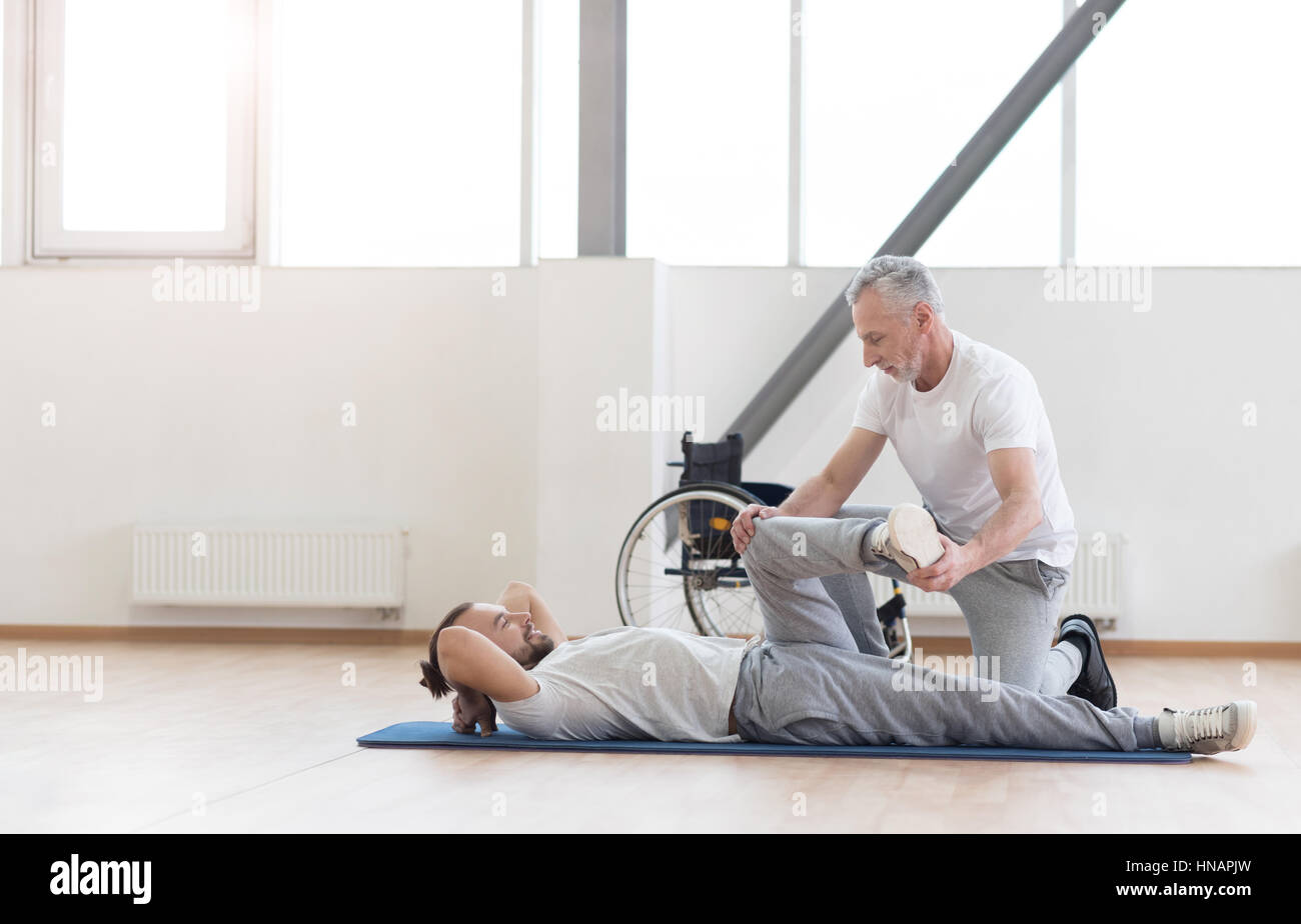 Proficient aged orthopedist working out with handicapped - Stock Image