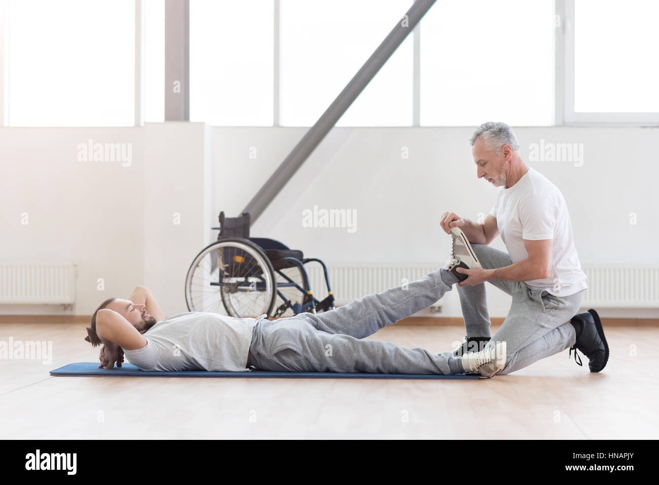 Concentrated aged orthopedist helping with disabled patient - Stock Image