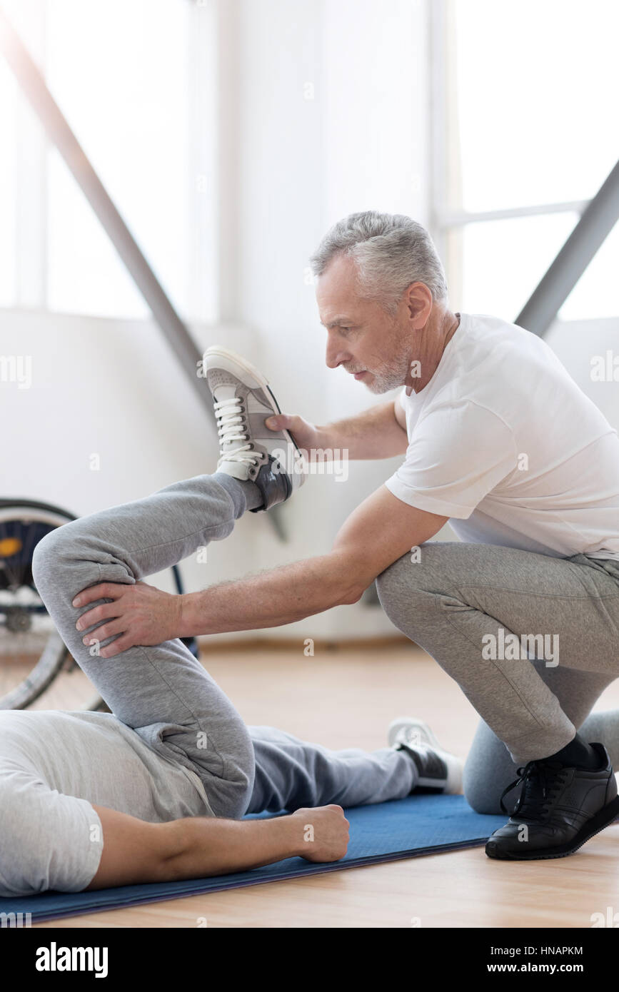 Powerful orthopedist stretching the handicapped in the gym - Stock Image