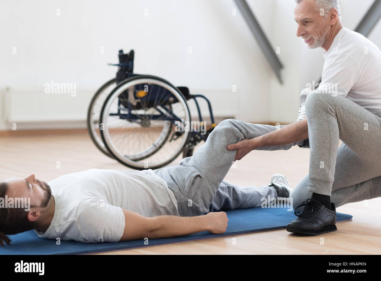 Charismatic orthopedist stretching the handicapped in the gym - Stock Image