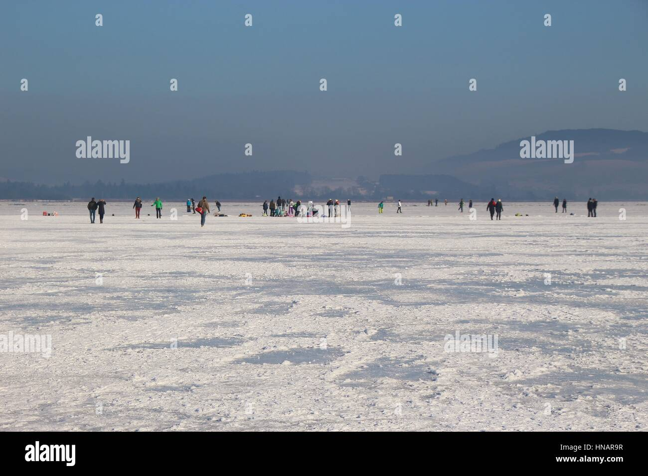 Many people on a Sunday stroll on  the frozen lake Wallersee in Seekirchen. Salzburger Land, Austria, Europe. - Stock Image
