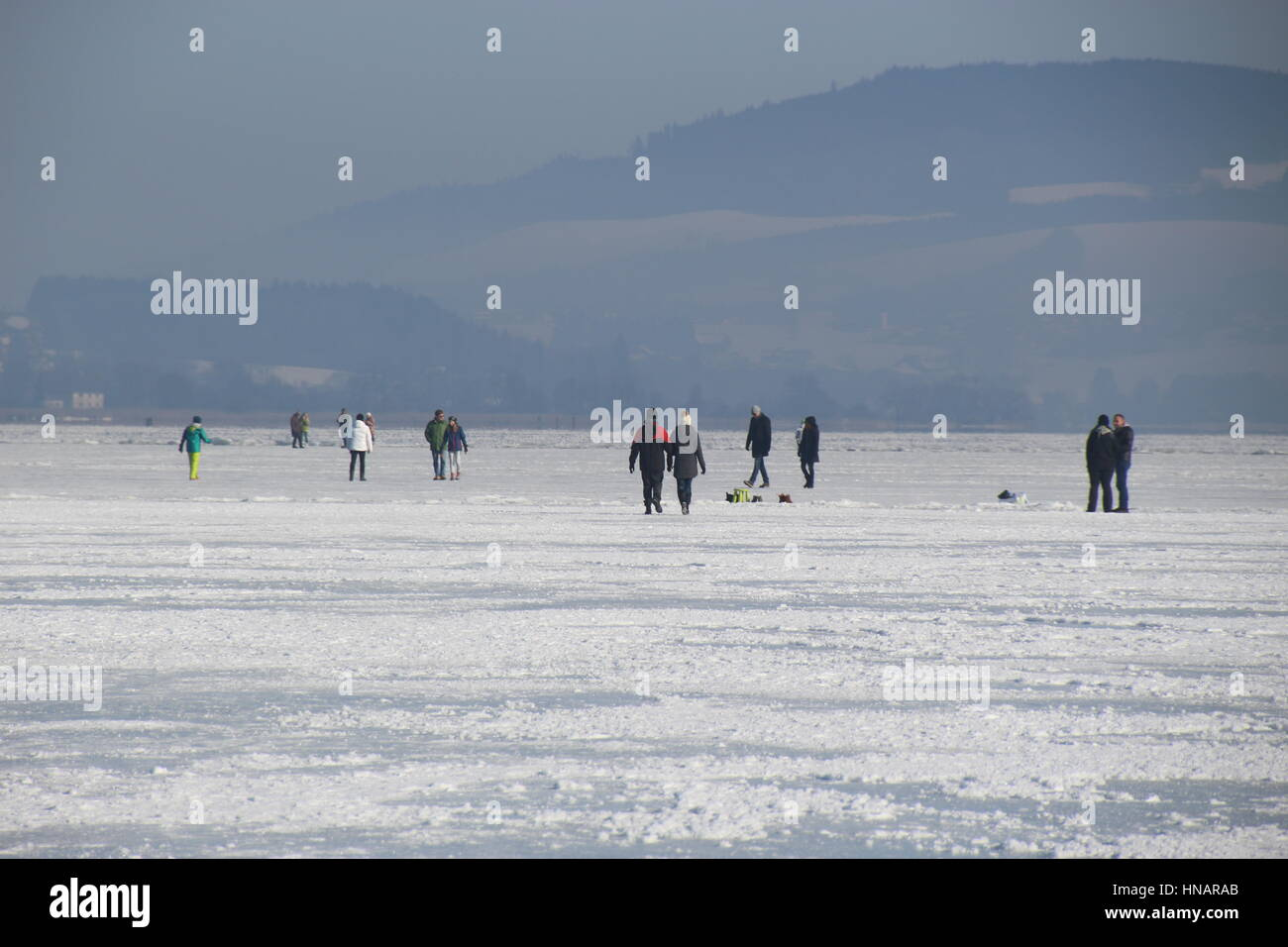 Many people walk on the frozen lake Wallersee in Seekirchen. Salzburger Land, Austria, Europe. - Stock Image